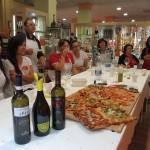 I partecipanti intorno al tavolo, alla fine del laboratorio, degustando il vino e mangiando la pizza